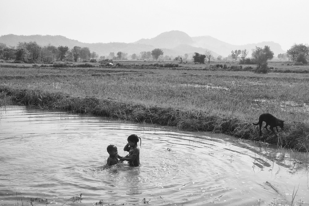 Children play in a ricefield runoff